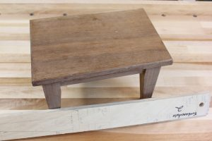 A footstool layout stick shows not only the dimensions of the project, but the details.
