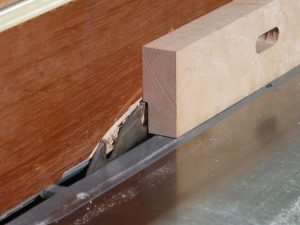 Use a flat top, rip blade to make the rabbet in the fence for the brass rub strip.