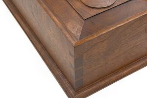 The corner of a document box with molded top edge that's mitered above the dovetails.